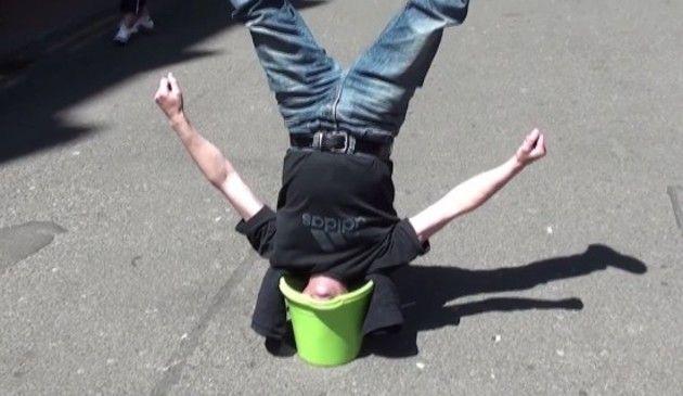 バケツに頭を突っ込んで逆立ちする大道芸人