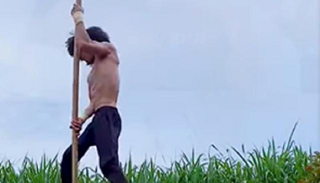 バランスと腕の力だけで固定されていない登り棒を登っていく男.png