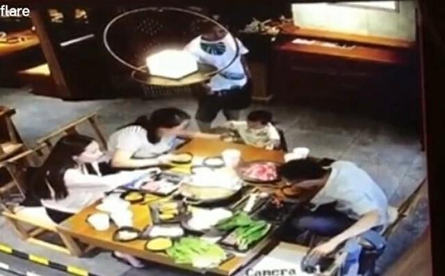 中国の中華レストランで熱々の鍋をかけられる男.jpg