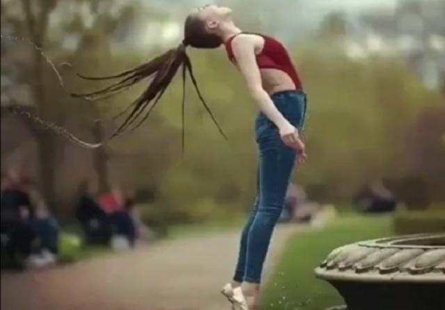 噴水前で女が髪の毛をあげる.png