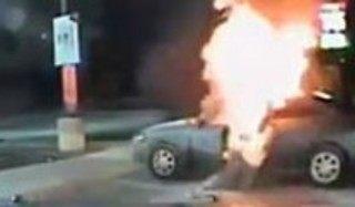 火のついた車に戻る男