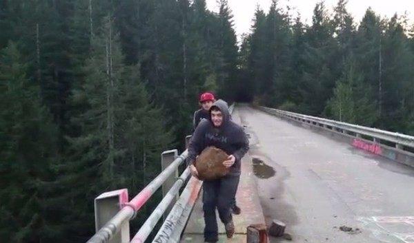 橋の上から石を落下させる男達